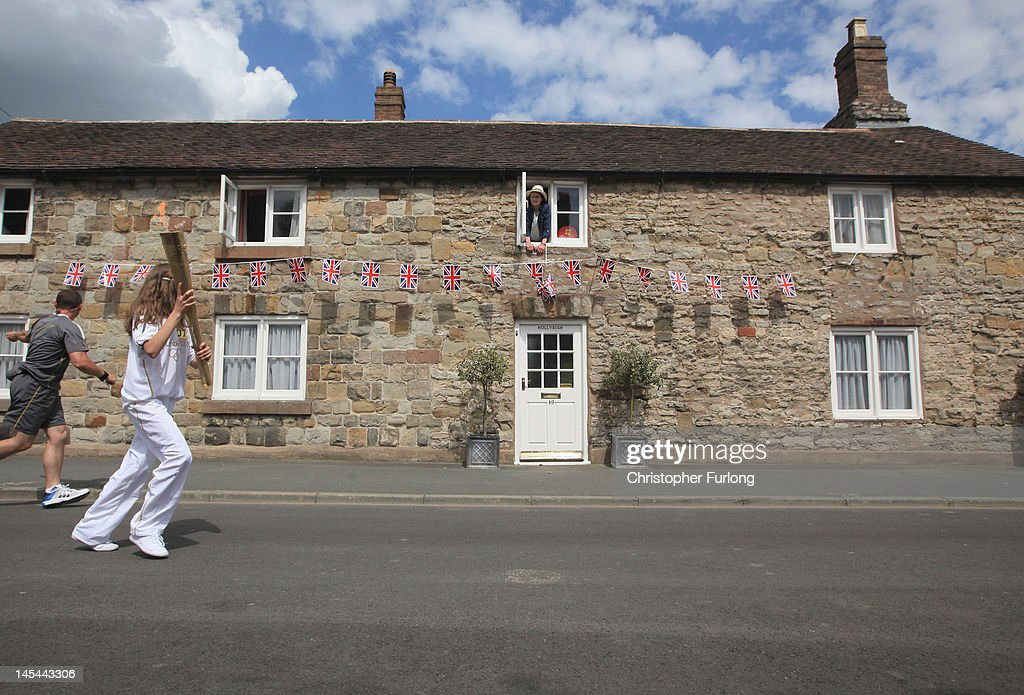 Resident Gabrielle Drake looks out of the window of Hollybush Cottage as the Olympic Torch passes through Much Wenlock the birthplace and former home of William Penny Brookes the founding father of the modern Olympics on May 30, 2012 in Much Wenlock, England. The Shropshire town of Much Wenlock is the birthplace of William Penny Brookes the founding father of the modern Olympics. The first Wenlock Olympian games were held in 1850 for 'every grade of man' amongst the athletic events it even included knitting and academic studies such as writing and arithmetic. Wenlock, one of the London 2012 mascots is named in honour of the Shropshire town.