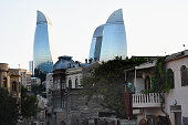 A resident hangs out a rug as The Flame Towers are seen at dusk on August 6 2014 in Baku Azerbaijan