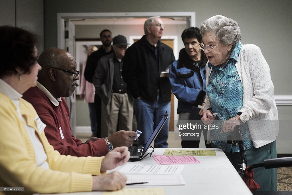 A resident has identification checked as she registers to vote in the South Carolina Republican presidential primary election at a polling station...