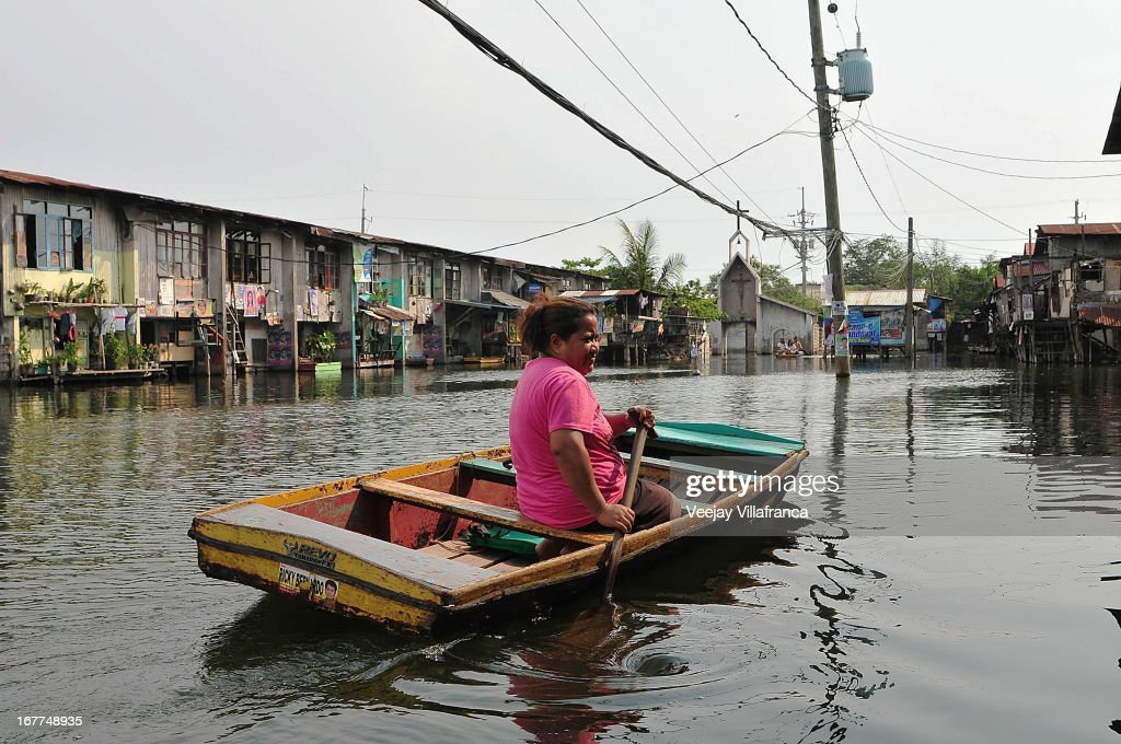 A resident heads home after ferrying passengers in her makeshift boat in Artex Compound in Malabon City on April 28, 2013 in Manila, Philippines. The residents of the former textile compound had to adjust their daily lives after flood waters submerged their low-lying village in 2004.