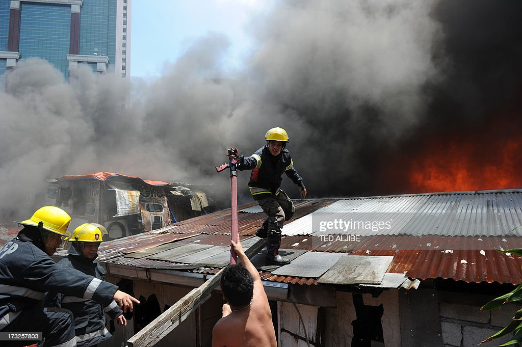 A resident helps firemen to put out a fire after a blaze engulfed a shanty town at the financial district of Manila on July 11, 2013. There were no immediate reports of casualties from the blaze, which occurred mid-morning amid government plans to relocate thousands of families living in areas vulnerable to floods and typhoons.
