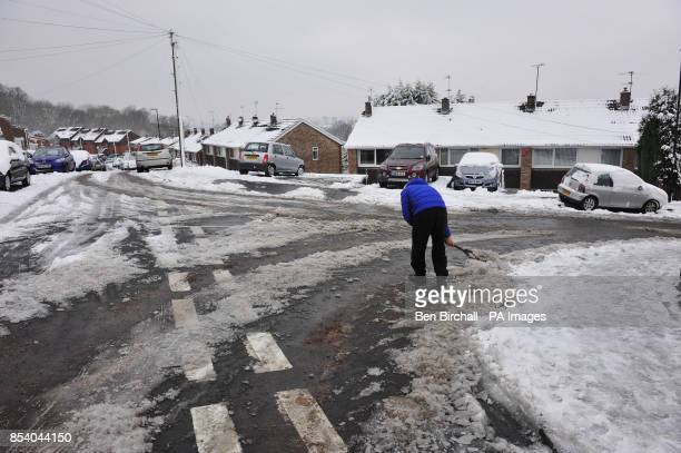 A resident helps to clear compact snow and ice from a residential culdesac at the top of a steep hill in Brislington Bristol PRESS ASSOCIATION Photo...