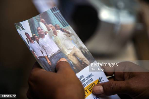 A resident holds a campaign pamphlet for Jose Manuel Olivares opposition coalition governor candidate for Vargas State during campaign visits in La...