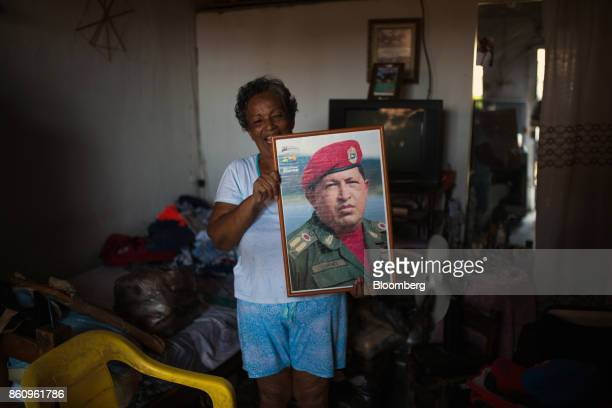 A resident holds a photograph of the late Venezuelan president Hugo Chavez while Jose Manuel Olivares opposition coalition governor candidate for...