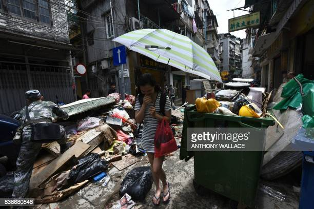 TOPSHOT A resident holds her nose due to the smell of rotting debris and garbage as a Chinese People's Liberation Army soldier based at a barracks in...