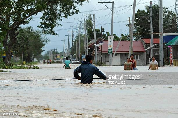 A resident holds onto a rope as he negotiates a flood current along a submerged highway in Santa Rosa town Nueva Ecija province north of Manila on...