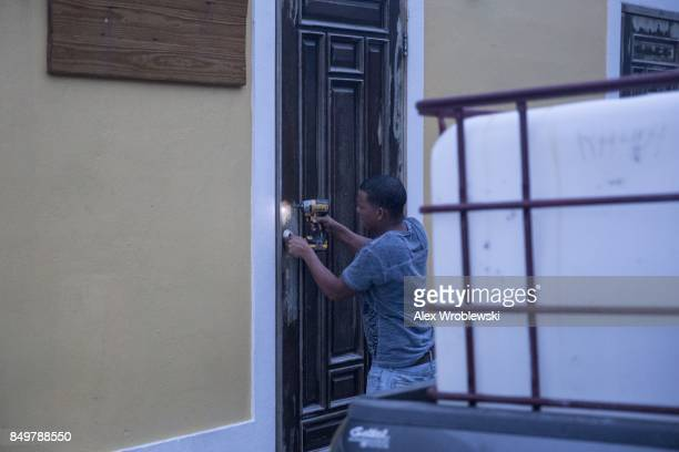 A resident in the La Perla neighborhood in Old San Juan secures a building as residents prepare for a direct hit from Hurricane Maria on September 19...