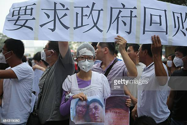 A resident injured by the explosions that hit a nearby chemical warehouse last week holds a photo of herself injured as she joins a protest outside...