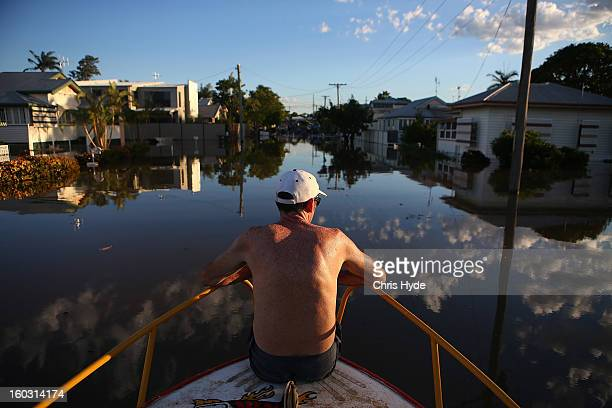 A resident inpects damage to houses as parts of southern Queensland experiences record flooding in the wake of Tropical Cyclone Oswald on January 29...