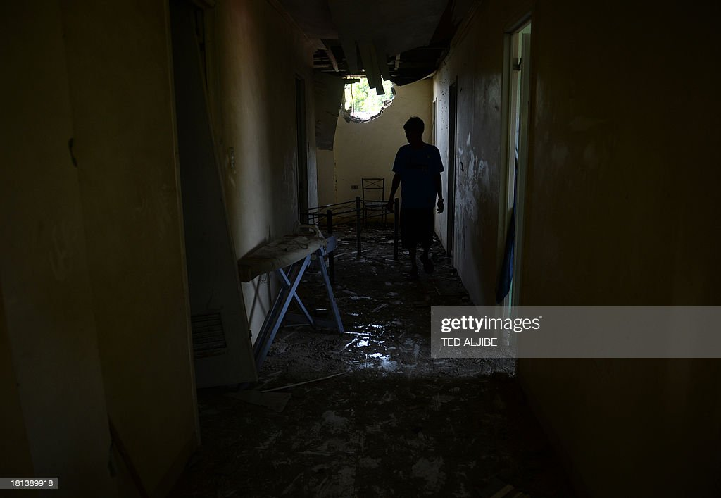 A resident inspects the damage to their house after a mortar shell believed to be from the Muslim rebels' position hit a residential house as government forces clash anew with remnants of Muslim rebels in Zamboanga City, on southern island of Mindanao on September 21, 2013. Philippine security forces killed eight Muslim rebels September 19, as they hunted the remnants of a guerrilla force hiding in homes of a major city and believed to be holding hostages.