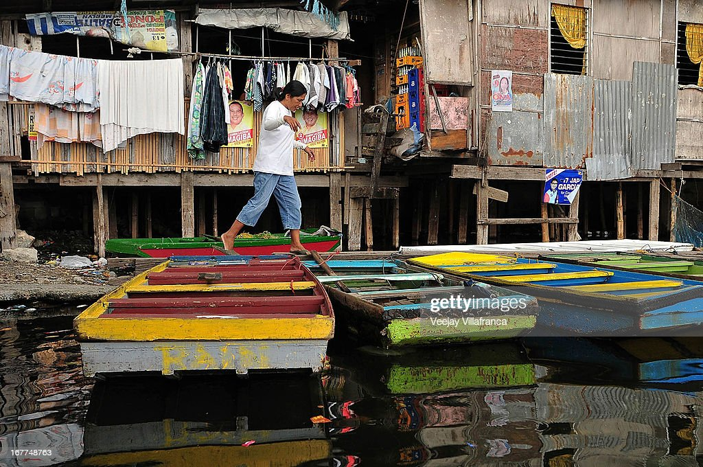 A resident jumps across makeshift boats in Artex Compound in Malabon City on April 28, 2013 in Manila, Philippines. The residents of the former textile compound had to adjust their daily lives after flood waters submerged their low-lying village in 2004.