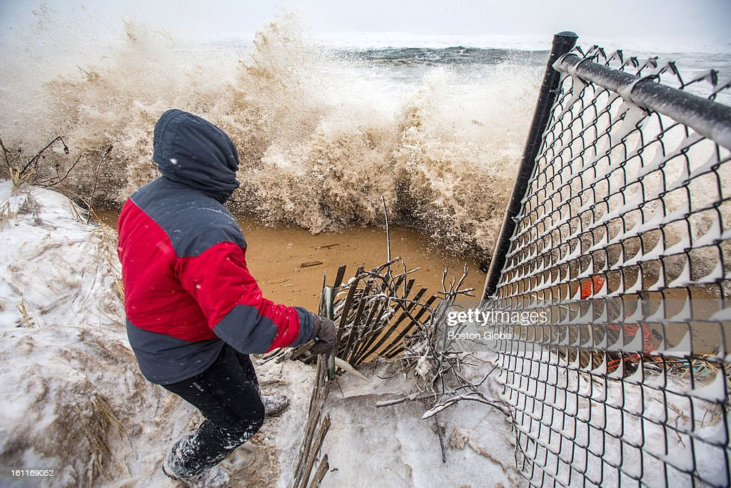 Resident Ken Smith braced himself as a large wave crashed against the sand barrier in front of him on Plum Island as a large winter storm hit the region.