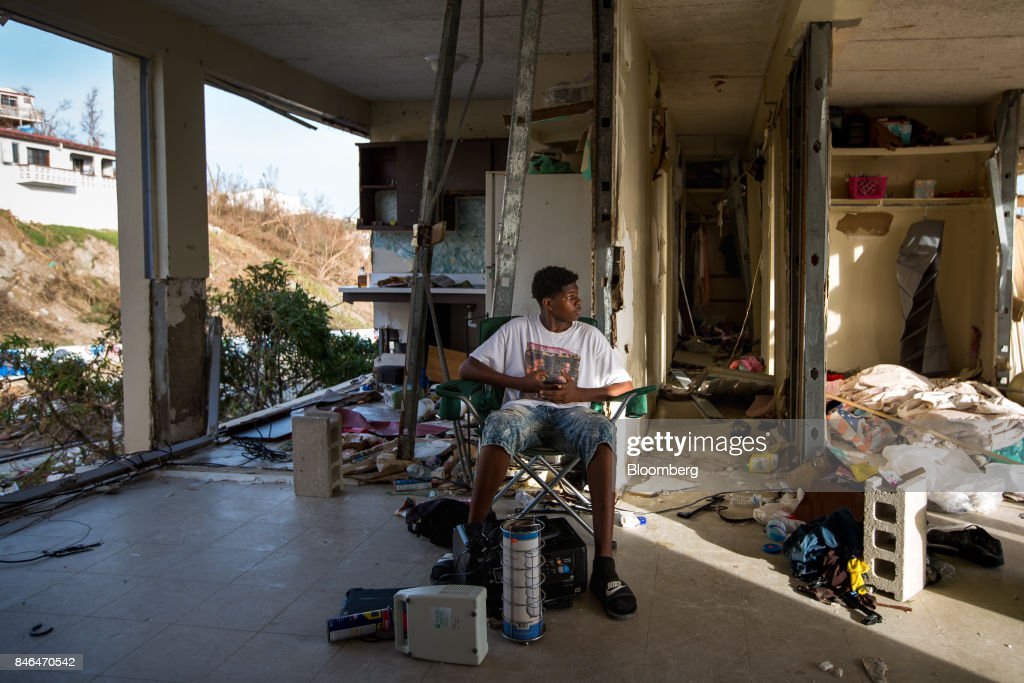 Resident Kimarley Brathweite, 13, sits in his grandmother's apartment damaged by Hurricane Irma in St Thomas, U.S. Virgin Islands, on Tuesday, Sept. 12, 2017. After being struck by Irma last week, the U.S. Virgin Islands couldn't look less like a tourist destination. Many local residents are giving up and getting out after losing everything to the category 5 storm,even as the local authorities in the U.S. territory say they are determined to rebuild the islands. Photographer: Michael Nagle/Bloomberg via Getty Images