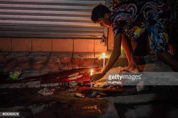 A resident lights candles on a pool of blood belonging to a suspected drug user who was shot dead by unknown assailants in Navotas north of Manila...