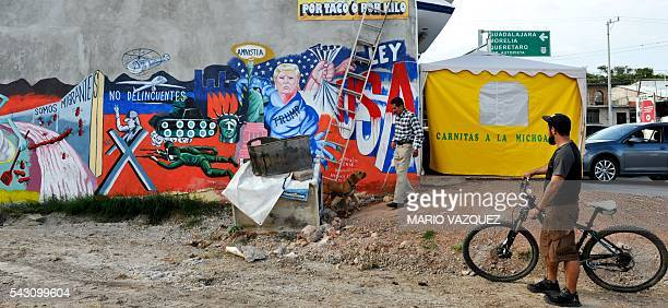A resident looks at a mural paint made by Mexican artist Luis Sotelo called 'We are migrants not criminals' in Tonatico Mexico on 25 June 2016 The...