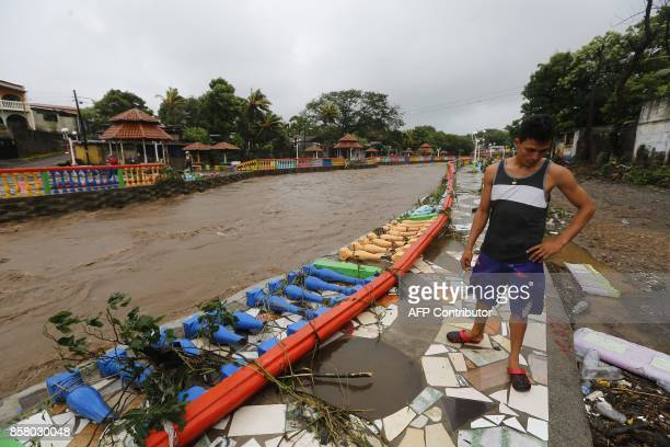 A resident looks at damages caused by the overflowing of the Masachapa River following the passage of Tropical Storm Nate in the city of Masachapa...