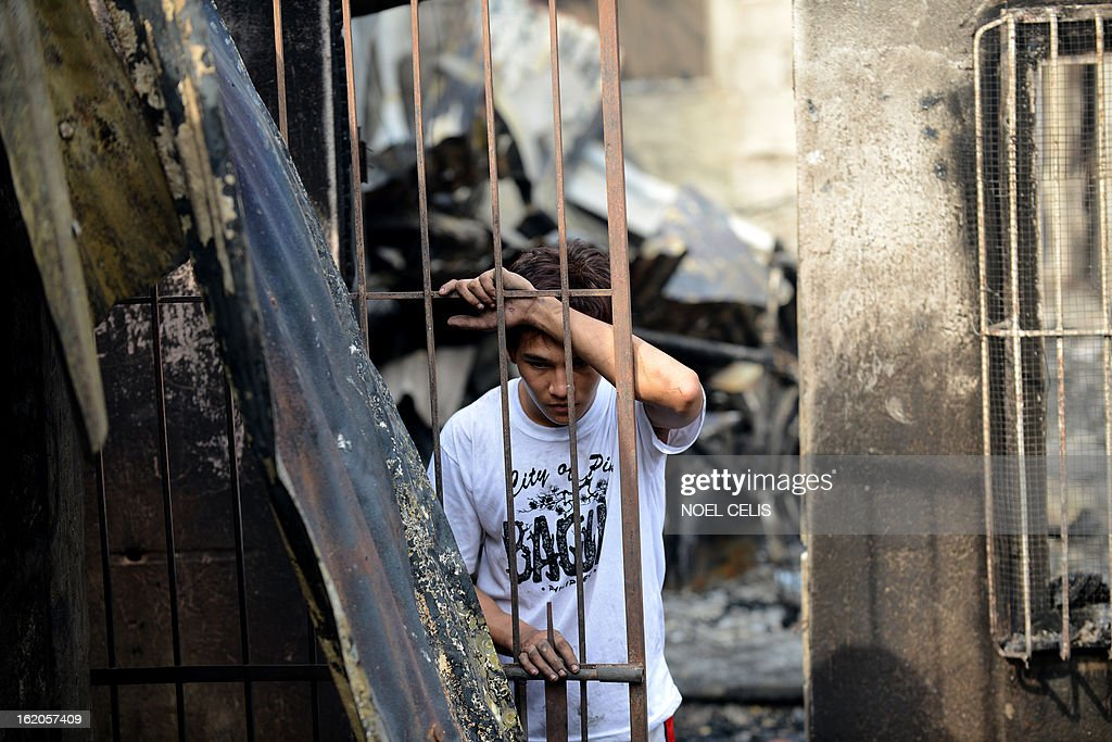A resident looks at debris of destroyed houses after an overnight fire in a slum area in Manila on February 19, 2013. Almost 500 houses were destroyed, leaving 2,000 residents homeless according to a local media report. AFP PHOTO/NOEL CELIS