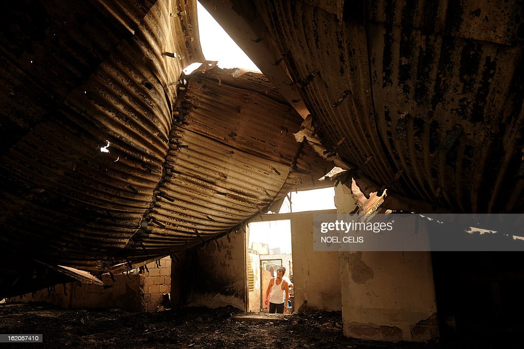 A resident looks at debris of destroyed houses after an overnight fire in a slum area in Manila on February 19, 2013. Almost 500 houses were destroyed, leaving 2,000 residents homeless according to a local media report.