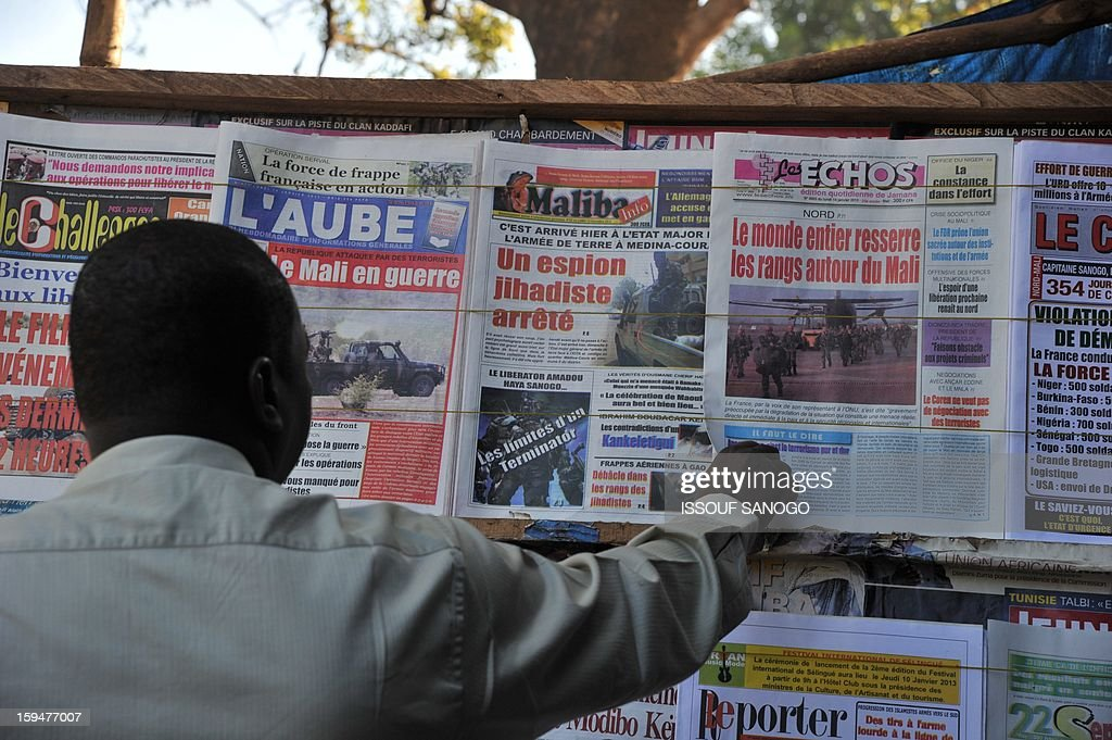 A resident looks at newspapers' frontpages focusing on France's military intervention to turn back the terrorist threat in Mali on January 14, 2013 in Bamako. AFP PHOTO /ISSOUF SANOGO
