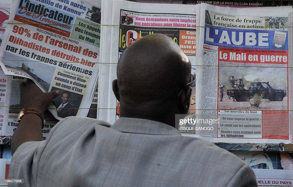 A resident looks at newspapers' frontpages focusing on France's military intervention to turn back the terrorist threat in Mali on January 14, 2013 in Bamako.