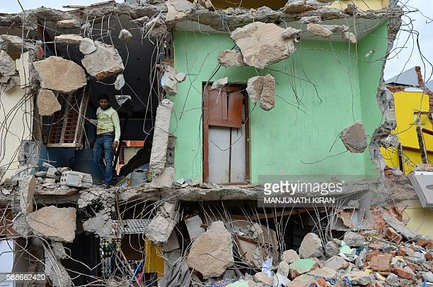 A resident looks at the debris of demolished houses a day after Bangalore's municipal authority Bruhat Bengaluru Mahanagara Palike brought down...