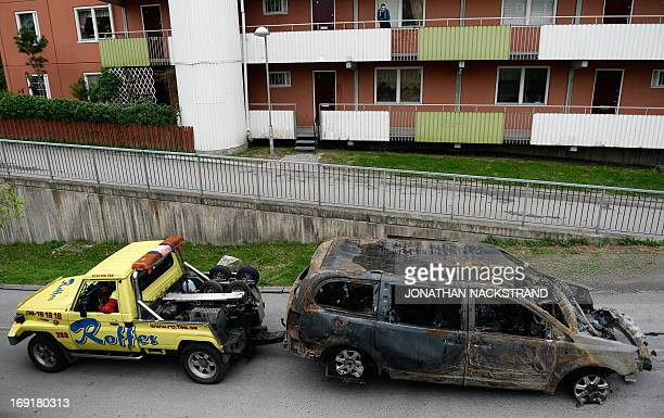 A resident looks on as a burnedout van is towed away after youths rioted in Husby northern Stockholm on May 21 2013 Youths in the immigrantheavy...