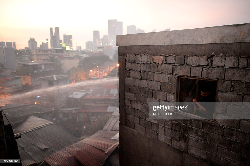 A resident looks on as firefighters try to put out a fire that swept over several houses in a residential area in Manila on May 3, 2016. No one was hurt in the fire, according to initial reports. / AFP / NOEL