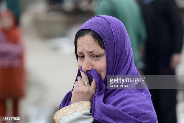 A resident looks on as waters rise in a neighbourhood of Srinagar on March 30 2015 At least 10 people have been buried by mudslides and hundreds more...
