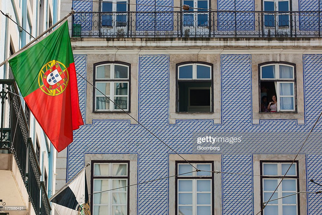A resident looks out from an old building above a Portuguese national flag on Figueira plaza in Lisbon, Portugal, on Wednesday, July 3, 2013. Portuguese borrowing costs topped 8 percent for the first time this year after two ministers quit, signaling the government will struggle to implement further budget cuts as its bailout program enters its final 12 months. Photographer: Mario Proenca/Bloomberg via Getty Images