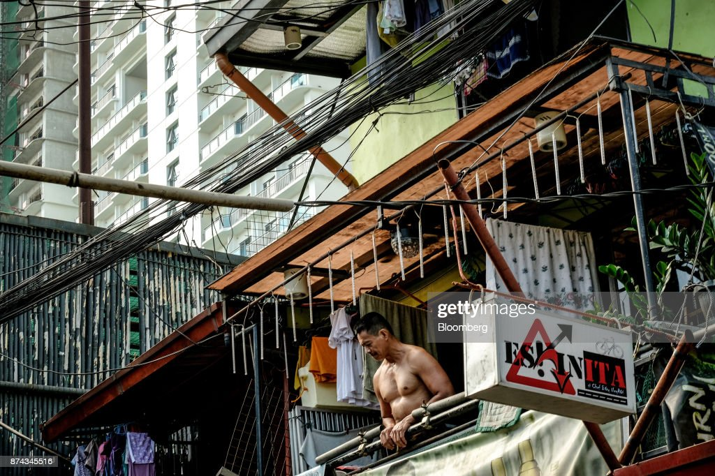 A resident looks out from low-cost housing as a residential development stands in the background in Mandaluyong, Metro Manila, Philippines, on Tuesday, Nov. 14, 2017. Economists are forecasting the Philippines to be among the first to raise interest rates in the region and the International Monetary Fund saidlast week the central bank should be ready to tighten if there are signs of overheating. Photographer: Veejay Villafranca/Bloomberg via Getty Images