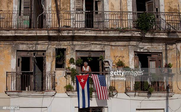 A resident looks out of a window as American and Cuban flags fly on the balcony of his home in Havana Cuba on Monday July 20 2015 A diplomatic freeze...