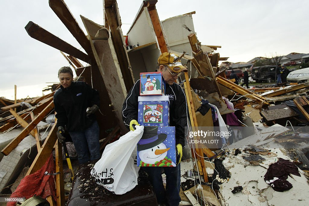 A resident moves some of his belongings from his destroyed home on May 21, 2013 in Moore, Oklahoma. Families returned to a blasted moonscape that had been an American suburb Tuesday after a monstrous tornado tore through the outskirts of Oklahoma City, killing at least 24 people. Nine children were among the dead and entire neighborhoods vanished, with often the foundations being the only thing left of what used to be houses and cars tossed like toys and heaped in big piles. AFP PHOTO/Joshua LOTT
