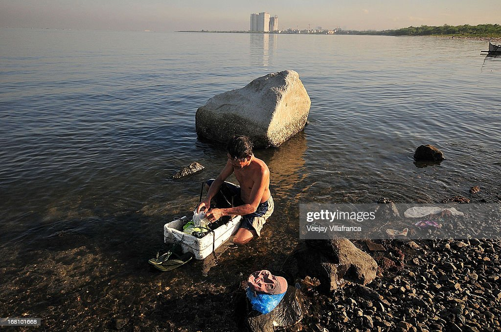 A resident of a nearby town gathers mussels and other shellfish and other on Freedom Island on May 5, 2013 in Manila, Philippines. Around 13,000 hectares of the coastal area is to be recalimed and developed under the Public Private Partnership (PPP) of the Philippine government.