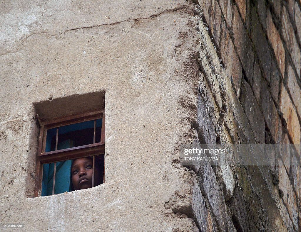 A resident of a neighbouring residential block looks from her window rescuers trying to evacuate a woman earlier discovered still alive on May 05, 2016 after being trapped for six-days in the rubble of a residential house that collapsed during torrential rain in Kenyan capital, Nairobi's low-income suburb of Huruma. The woman was pulled out hours after being located on May 5, 2016 morning by rescuers who gave her oxygen while they continued efforts to extract her from the ruins of the six-storey building. / AFP / TONY