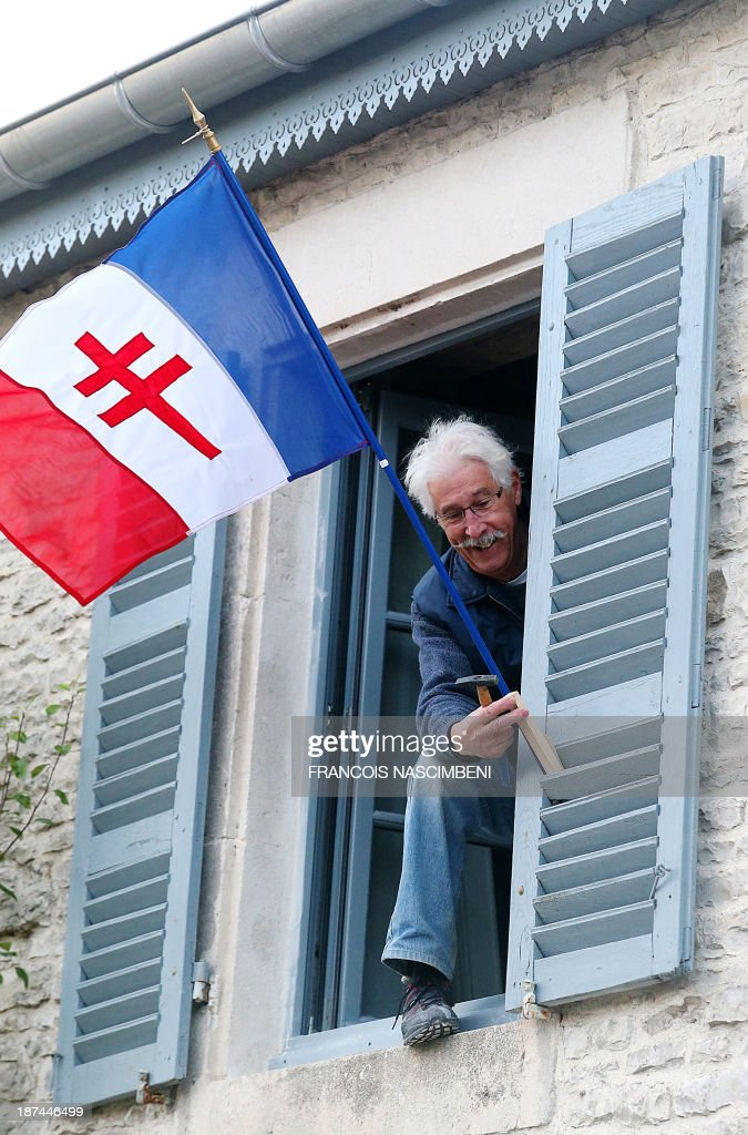 A resident of Colombey-les-deux-Eglises hangs on November 9, 2013 the flag of Free France (a French flag featuring a red Cross of Lorraine) during a ceremony marking the 43rd anniversary of the death of late French President, General Charles De Gaulle. PHOTO