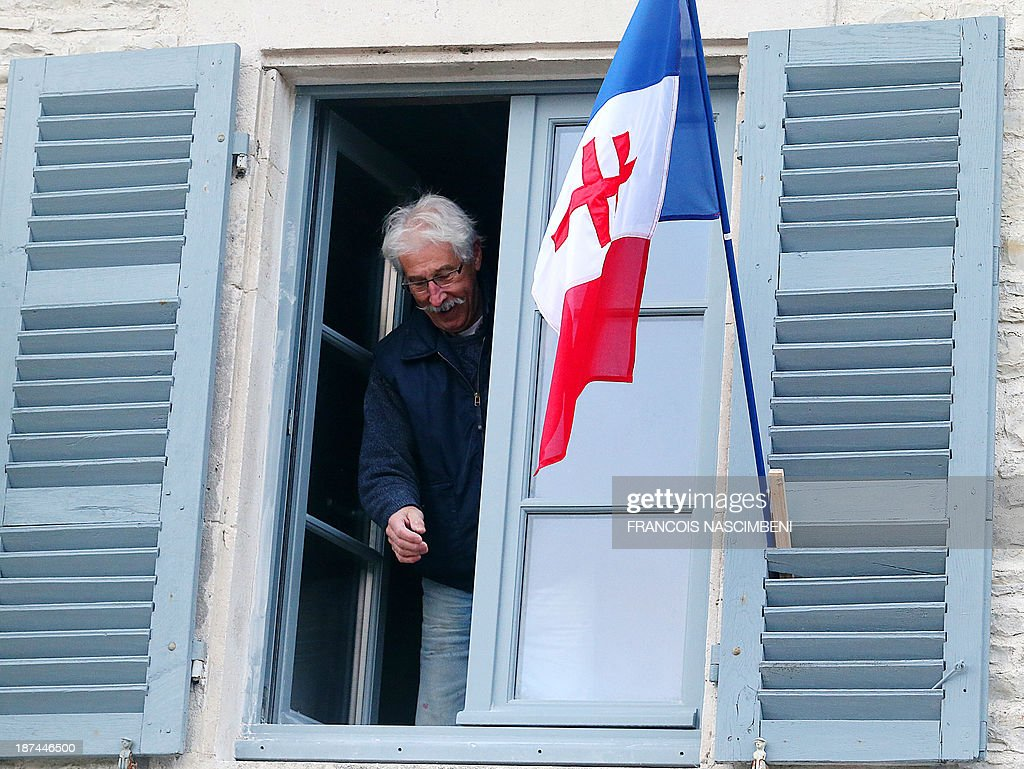 A resident of Colombey-les-deux-Eglises hangs on November 9, 2013 the flag of Free France (a French flag featuring a red Cross of Lorraine) during a ceremony marking the 43rd anniversary of the death of late French President, General Charles De Gaulle. PHOTO AFP -FRANCOIS NASCIMBENI