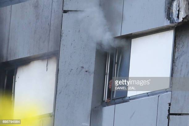 TOPSHOT A resident of Grenfell Tower is trapped as smoke billows from the window after a fire engulfed the building on June 14 2017 in west London...