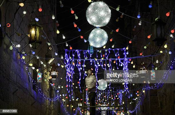 A resident of Jerusalem decorates a street with traditional festive lights ahead of the start of the Muslim holy month of Ramadan on August 20 2009...