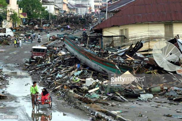 Resident of Meulaboh city the hardest area hit by the 90 earthquake and tsunamis a week ago pass by the ruins in West Aceh 01 January 2005...