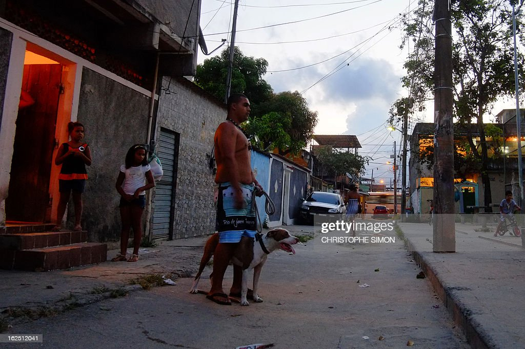 A resident of Rio de Janeiro's Cidade de Deus shantytown stands with his pit bull dog, on February 23, 2013. AFP PHOTO/Christophe Simon
