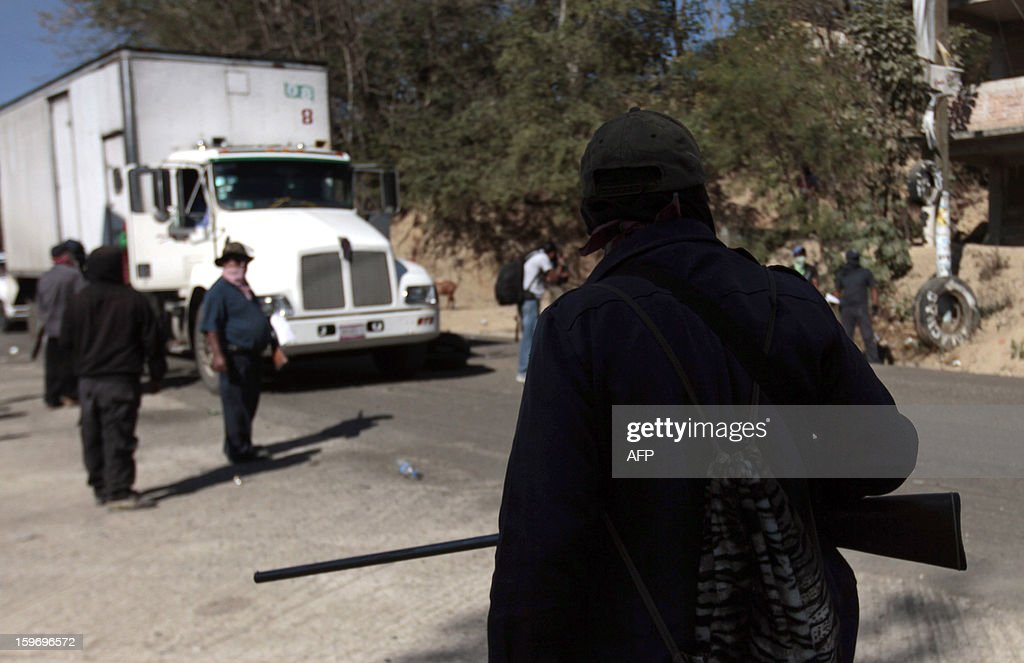 A resident of Tecoanapa, in the Mexican southern state of Guerrero, forming their own vigilante police forces, stands guard at a checkpoint in the main access to the nearby village of Pericon on January 18, 2013. Hundreds of civilians armed with rifles, pistols and machetes decided to provide security for the communities of Tecoanapa and Ayutla de los Libre in the state of Guerrero, saying gangs were committing robberies, kidnappings and murder. The vigilante force has put up checkpoints on roads and conducts night watches in the towns. Guerrero, home to the Pacific resort town of Acapulco, has been one of the states hardest hit by Mexico's drug violence, which has left more than 70,000 people killed across the country since 2006. AFP PHOTO/Pedro Pardo