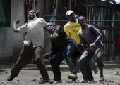 Resident of the Mathare slum of Nairobi throw rocks at Kenyan police 17 January 2008 Kenyan police shot two people dead in a Nairobi slum Thursday an...
