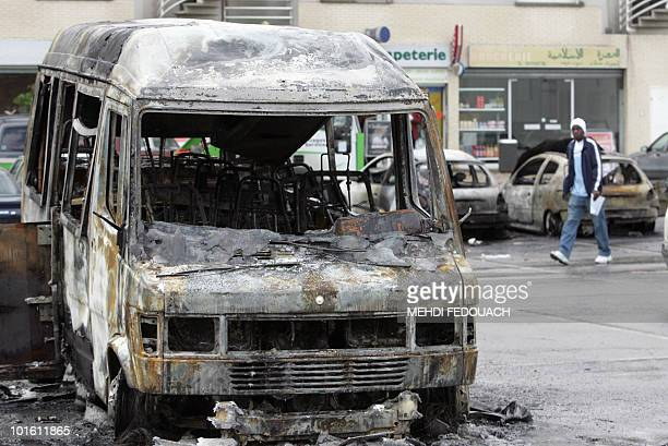 A resident of the Maurice Thorez neighborhood walks by a burned car 04 November 2005 in Trappes Gang of youths torched more than 500 cars overnight...