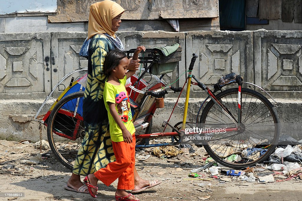 A resident of the Muara Angke fisherman village and a child walk with packages of rice and bottles of syrup for Eid Al-Fitr donated by Jakarta's governor Joko Widodo, in Jakarta on August 4, 2013. Indonesian Muslim people will celebrate Eid Al-Fitr festival on the first day of Shawwal in the Islamic calender to mark the end of the holy month of Ramadan.