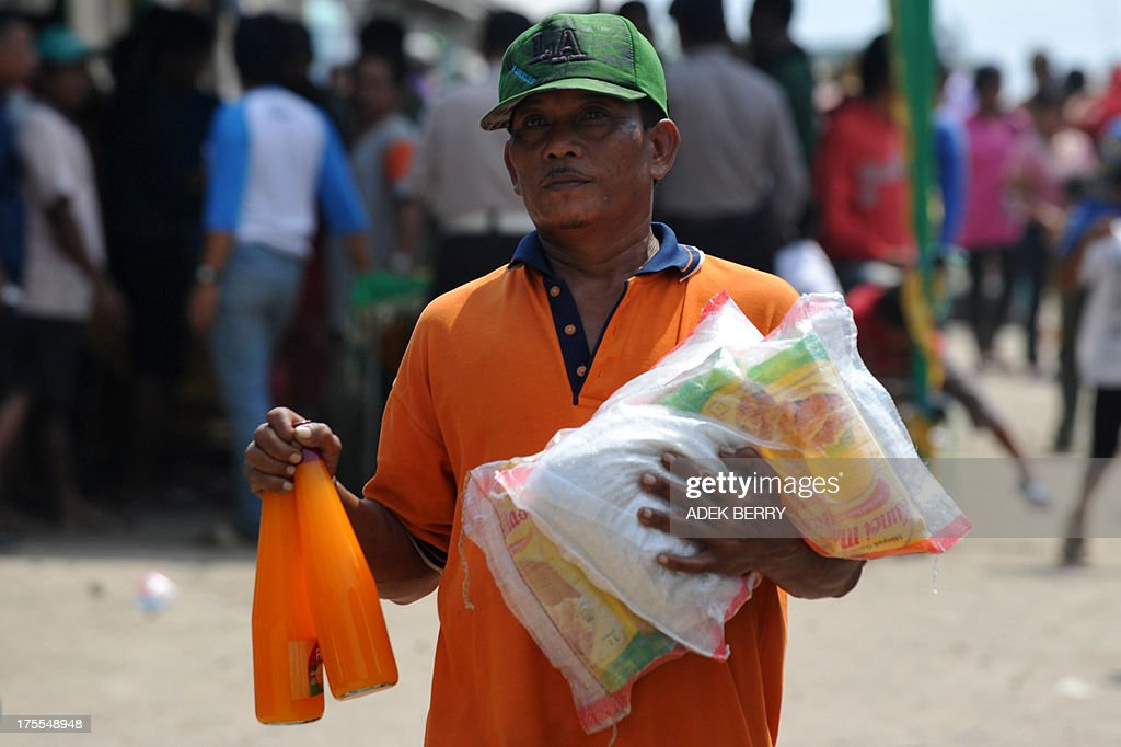 A resident of the Muara Angke fisherman village carries packages of rice and two bottles of syrup for Eid Al-Fitr donated by Jakarta's governor Joko Widodo, in Jakarta on August 4, 2013. Indonesian Muslim people will celebrate Eid Al-Fitr festival on the first day of Shawwal in the Islamic calender to mark the end of the holy month of Ramadan. AFP PHOTO / ADEK BERRY
