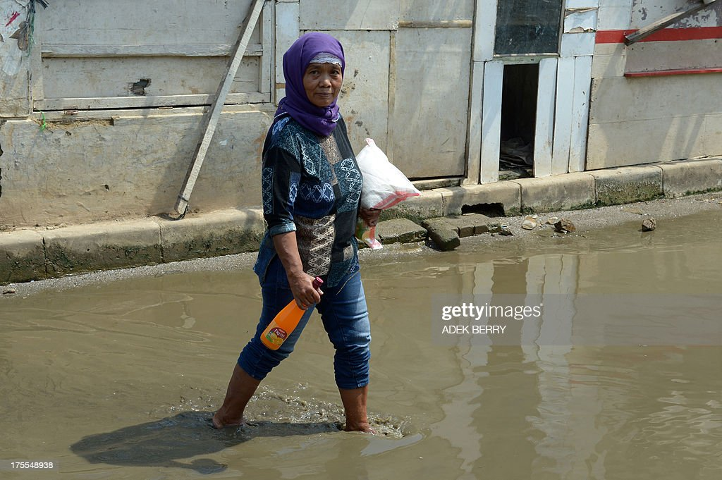 A resident of the Muara Angke fisherman village walks through water in the street from recent rains carrying a package of rice and a bottle of syrup for Eid Al-Fitr donated by Jakarta's governor Joko Widodo, in Jakarta on August 4, 2013. Indonesian Muslim people will celebrate Eid Al-Fitr festival on the first day of Shawwal in the Islamic calender to mark the end of the holy month of Ramadan.