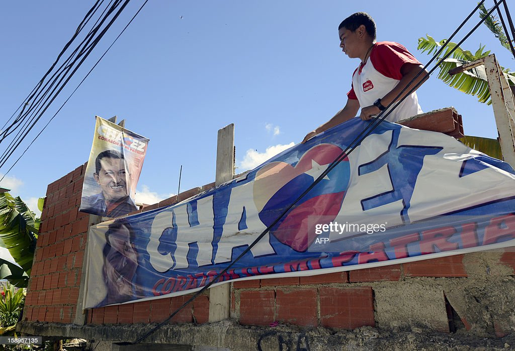 A resident of the popular sector of San Agustin hangs a banner of Venezuelan President Hugo Chavez in Caracas on January 4, 2013. Hugo Chavez's top aides have gone on the offensive, accusing the opposition and media of waging a 'psychological war,' as Venezuela's cancer-stricken president battles a serious lung infection. The closing of ranks followed a high-level gathering of top Venezuelan officials in Havana with Chavez, amid growing demands to know whether he will be fit on January 10 to take the oath of office for another six-year-term. AFP PHOTO/Leo Ramirez