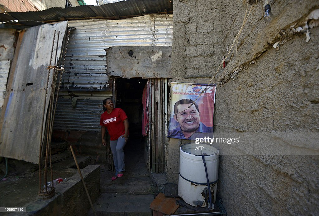 A resident of the popular sector of San Agustin walks outside her home next to a poster of Venezuelan President Hugo Chavez in Caracas on January 4, 2013. Hugo Chavez's top aides have gone on the offensive, accusing the opposition and media of waging a 'psychological war,' as Venezuela's cancer-stricken president battles a serious lung infection. The closing of ranks followed a high-level gathering of top Venezuelan officials in Havana with Chavez, amid growing demands to know whether he will be fit on January 10 to take the oath of office for another six-year-term. AFP PHOTO/Leo Ramirez