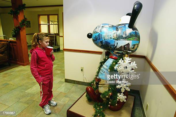 A resident of the Ronald McDonald House looks at a statue of Snoopy during the NBA Holiday Food Drive at the Ronald McDonald House on December 11...