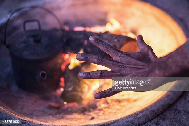 A resident of the tent embassy warms his hands on a fire in Redfern on August 9 2015 in Sydney Australia The tent embassy was established in March...